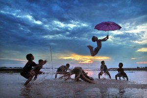 Children play in the water after school in Cooch Behar, India.